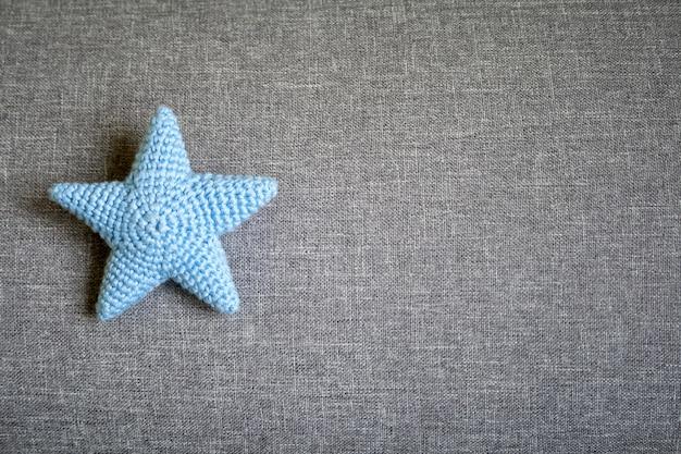 Niebieska dzianinowa gwiazda na szarym tle tekstylnym
