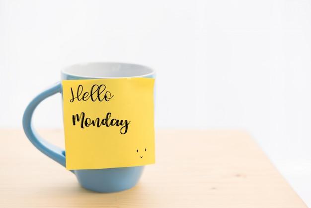 """Niebieska filiżanka kawy i karteczka samoprzylepna z napisem """"hello monday"""", na drewnianym stole"""