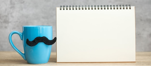 Niebieska filiżanka kawy lub kubek herbaty z czarnym wystrojem wąsów i pusty papierowy notatnik lub kalendarz na stole. pusta kopia miejsca na tekst. niebieski listopad, szczęśliwy dzień ojca i koncepcja międzynarodowego dnia mężczyzn