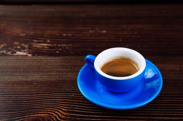 Niebieska filiżanka kawy na drewnianym stole