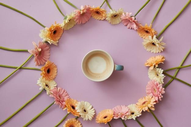 Niebieska filiżanka kawy w okrągłej ramce z kolorowych kwiatów gerbery na różowym tle z koncepcją z dnia matki