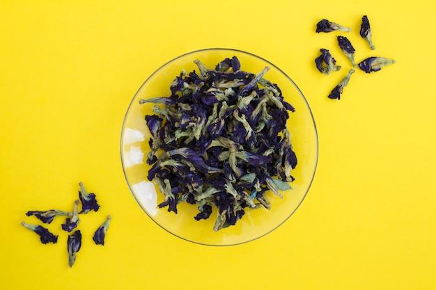 Niebieska herbata kwiatowa w szklanym spodku pośrodku żółtego tła. widok z góry. skopiuj miejsce.