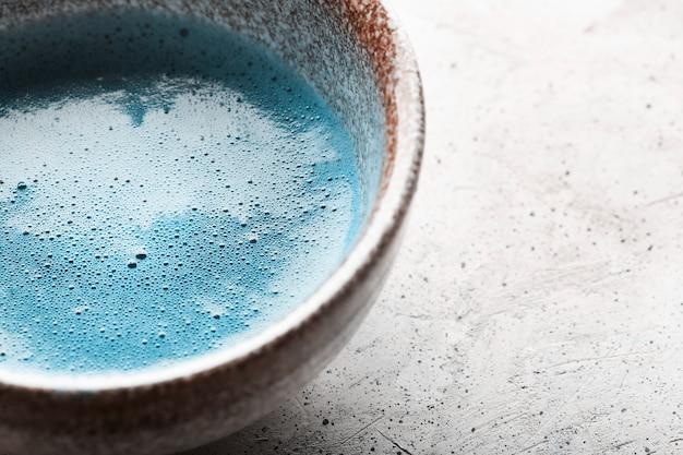 Niebieska herbata matcha w miseczkach i chasen na betonowej powierzchni