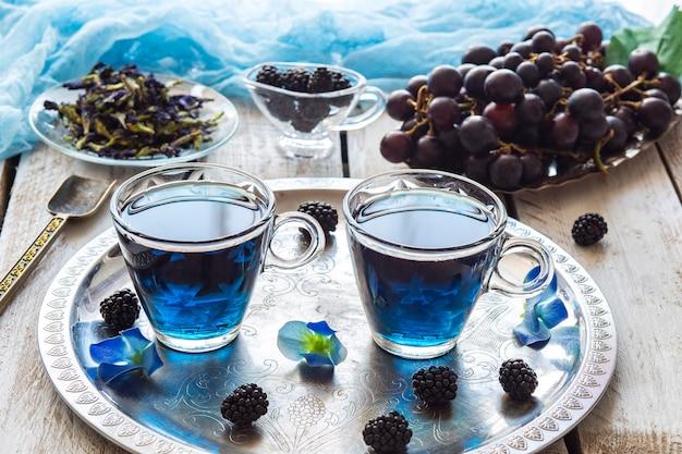 Niebieska herbata w przezroczystych filiżankach, jeżynach i winogronach, łyżka do herbaty i spawania