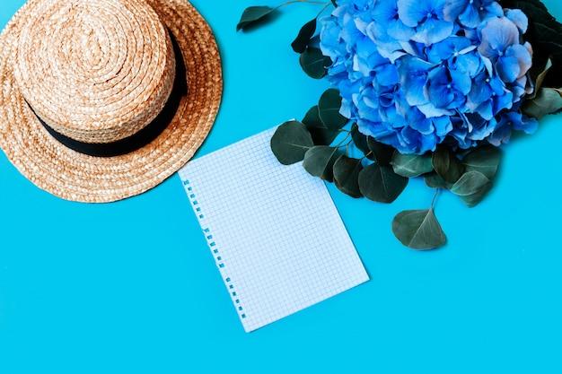 Niebieska hortensja widok z góry ściana pozostawia bukiet kapelusz aparat fotograficzny podkładka notatnik strona rwie