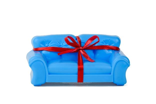 Niebieska kanapa związana z czerwoną wstążką na białym tle. próbka pięknych mebli do domu. minimalistyczny.