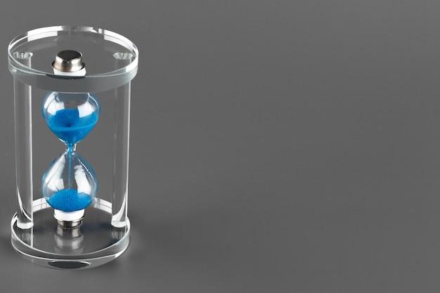 Niebieska klepsydra na szarej powierzchni z bliska