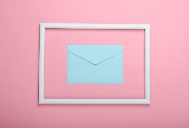 Niebieska koperta w białej ramce na różowej powierzchni