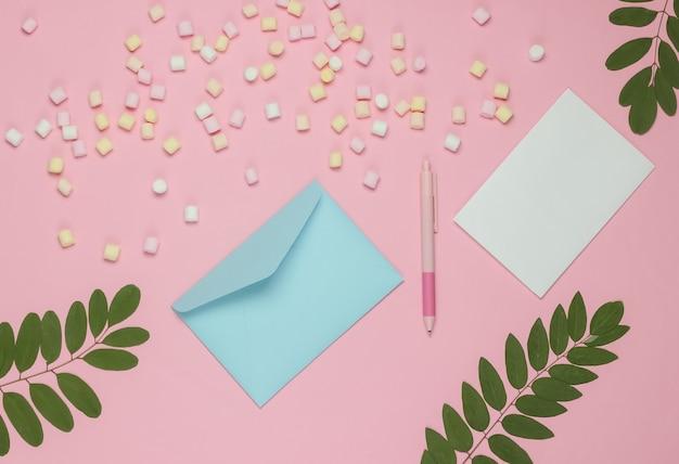 Niebieska koperta z piórem i piankami na różowym tle. płaska makieta na walentynki, ślub lub urodziny. widok z góry