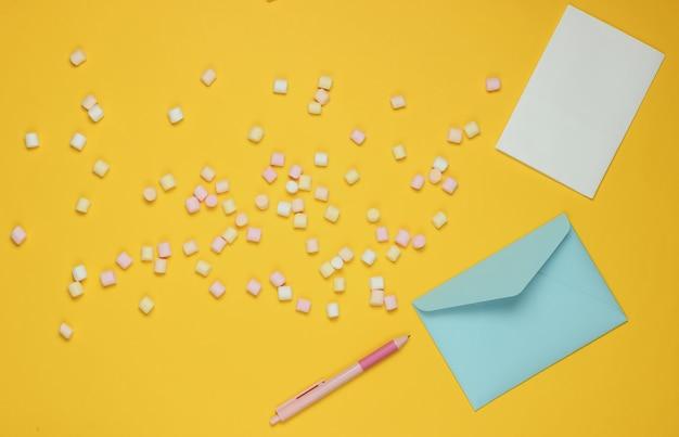 Niebieska koperta z piórem i piankami na żółtym tle. płaska makieta na walentynki, ślub lub urodziny. widok z góry