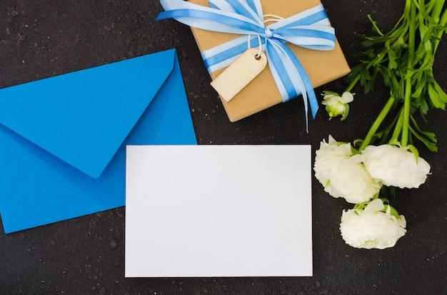 Niebieska koperta z pustym białym papierem i prezentem