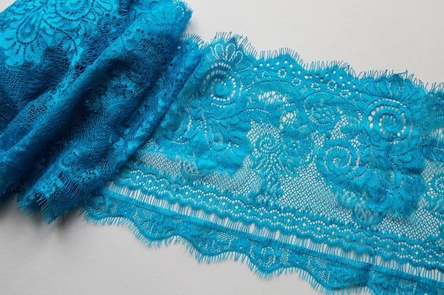Niebieska koronka leżąca na białej powierzchni