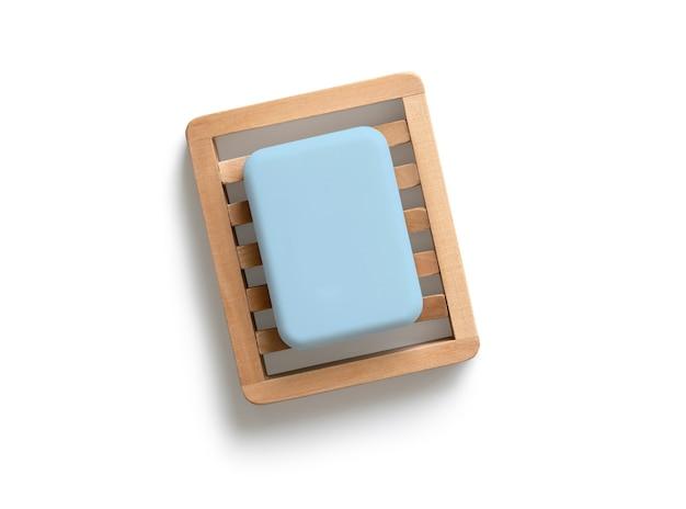 Niebieska kostka mydła na drewnianej mydelniczce na białym tle na białym tle.