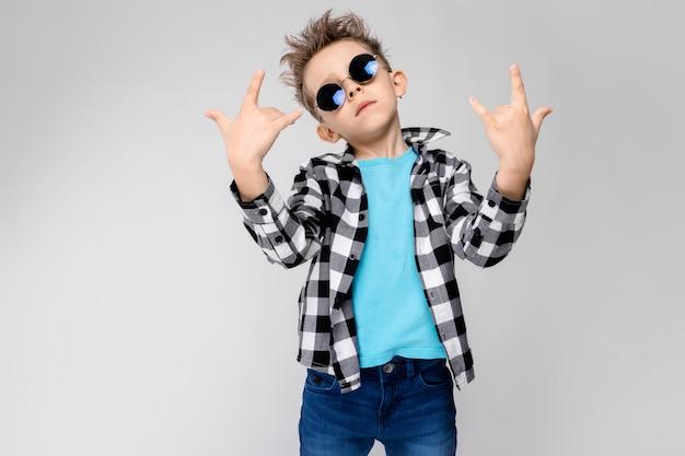 Niebieska koszula i jeansy stoją na szarym tle. chłopiec ma na sobie okrągłe okulary. rudzielec pokazuje kozła bujanego