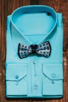 Niebieska koszula męska z ornamentem muszką na drewnianym biurku