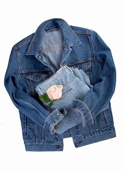 Niebieska kurtka dżinsowa i spodnie, róża na białym tle na białej powierzchni