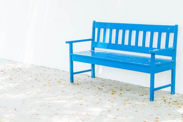 Niebieska ławka z białą ścianą