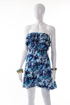 Niebieska letnia sukienka na manekinie. żeński manekin sobie cienką sukienkę. niebieski ubiór z małą zawieszką. cenny dodatek i sukienka damy.