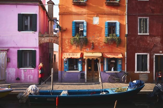 Niebieska łódź na rzece w pobliżu pomarańczowego budynku