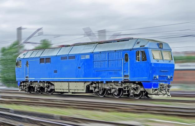Niebieska lokomotywa pociąg z silnikiem wysokoprężnym z dużą prędkością jeździ koleją.