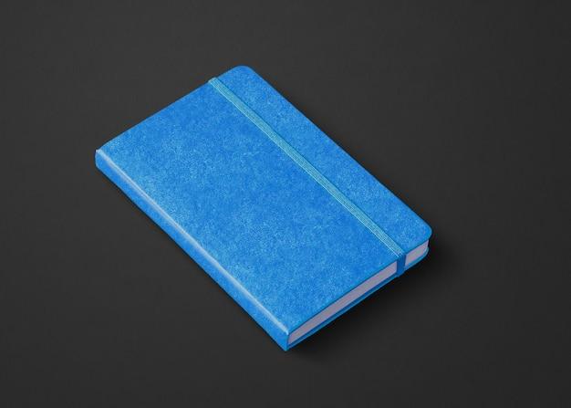 Niebieska makieta zamkniętego notebooka na czarnym tle