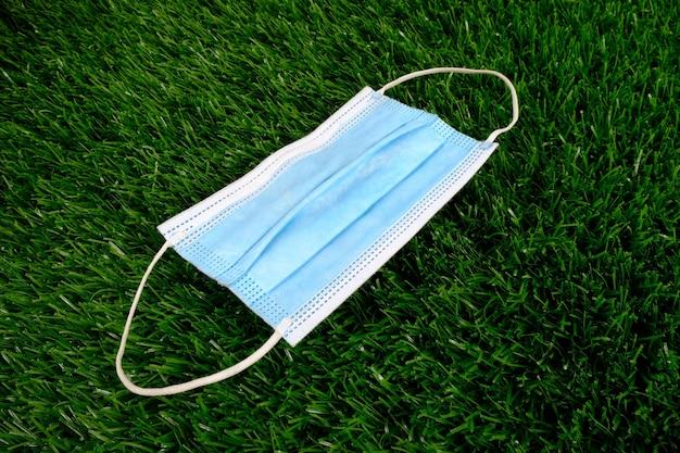 Niebieska maska medyczna na zielonej trawie.
