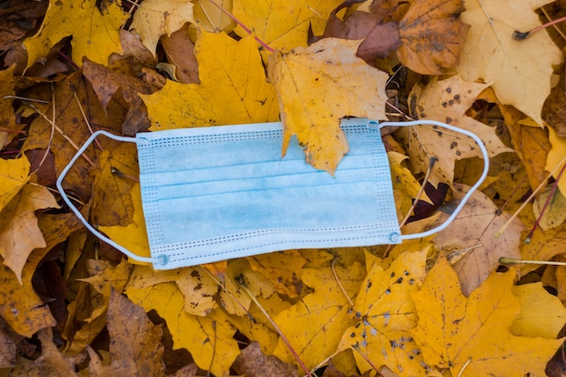 Niebieska maska na twarz leży w jesiennych żółtych liściach w zbliżeniu