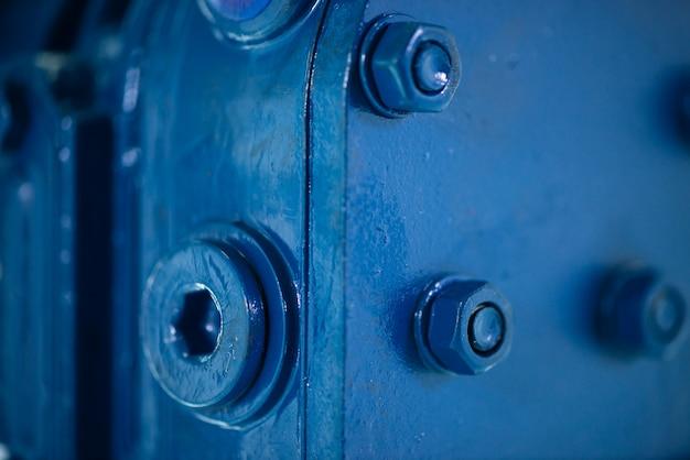 Niebieska metalowa szorstka powierzchnia części ze śrubami i nakrętkami. niebieski lakier części samochodowej.