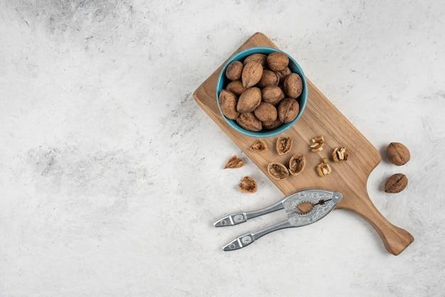 Niebieska miska całych orzechów włoskich na drewnianej desce do krojenia.