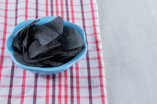 Niebieska miska chrupiących czarnych frytek i obrus na kamieniu.