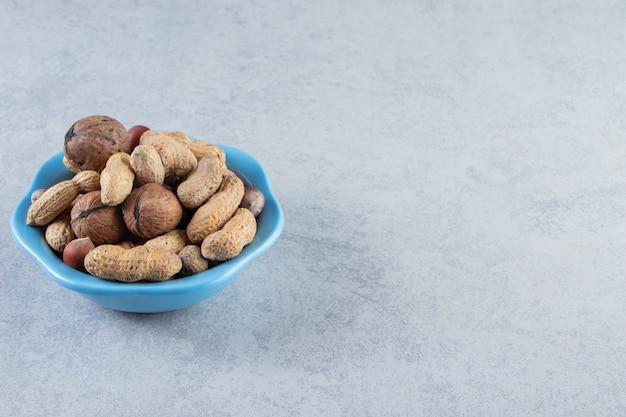 Niebieska miska organicznych orzechów umieszczona na tle kamienia.