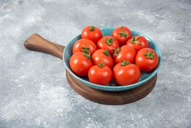 Niebieska miska pełna czerwonych świeżych pomidorów na marmurze.