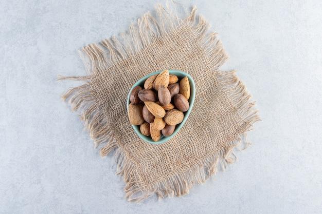 Niebieska miska pełna łuskanych migdałów i orzechów włoskich na tle kamienia.