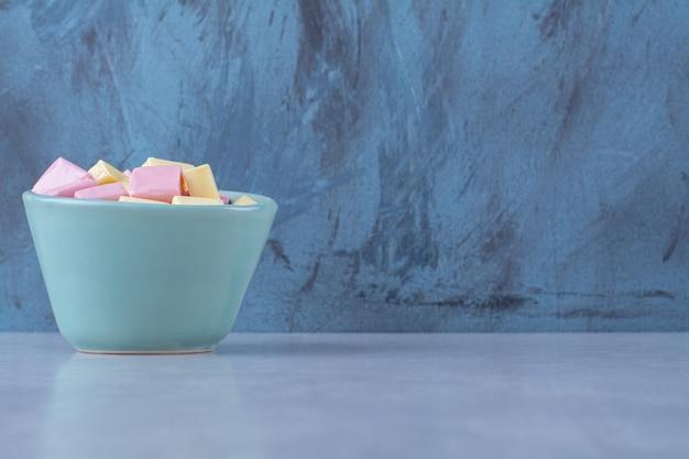 Niebieska miska pełna różowo-żółtych słodkich wyrobów cukierniczych pastila.