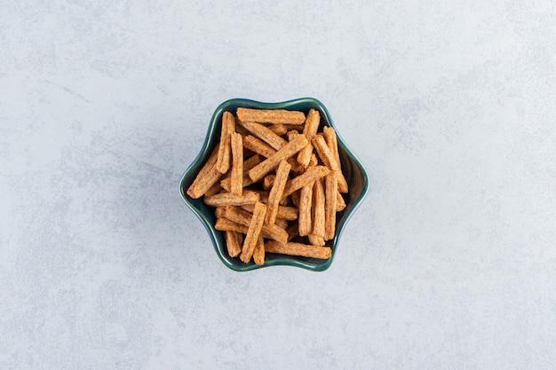 Niebieska miska smacznych krakersów kij na tle kamienia.