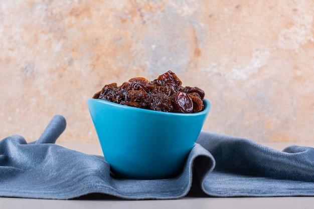 Niebieska miska suszonych śliwek organicznych umieszczona na białym tle. zdjęcie wysokiej jakości