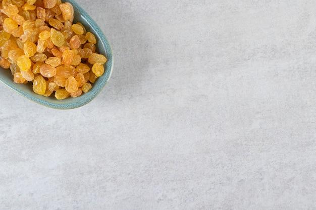 Niebieska miska z suszonymi złotymi rodzynkami na kamiennej powierzchni