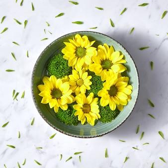 Niebieska miska z wiosenną kompozycją kwitnącą z kwiatów w wodzie na marmurowym tle, pokrytym zielonymi płatkami kwiatów.
