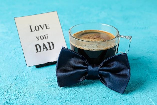 Niebieska muszka, filiżanka kawy i napis kocham cię tato na kolor tła, miejsca na tekst