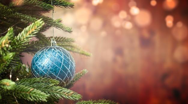 Niebieska ozdoba świąteczna na drzewie na tle bożonarodzeniowych lampek