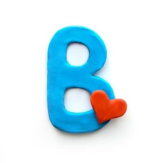 Niebieska plastelina litera b alfabet angielski z czerwonym sercem oznacza miłość