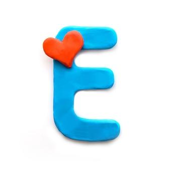 Niebieska plastelina litera e alfabet angielski z czerwonym sercem oznacza miłość