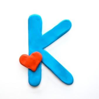 Niebieska plastelina litera k alfabetu angielskiego z czerwonym sercem oznacza miłość