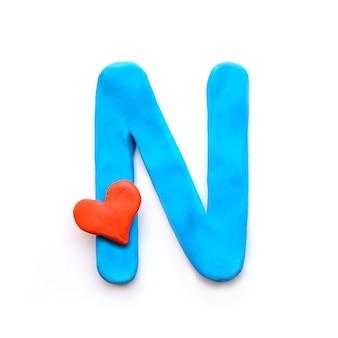 Niebieska plastelina litera n alfabet angielski z czerwonym sercem oznacza miłość