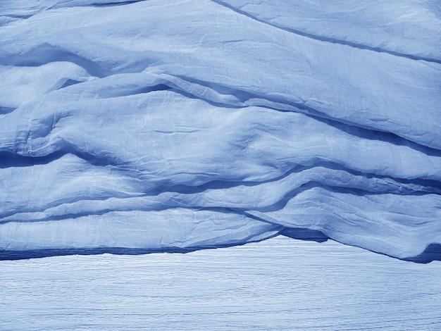 Niebieska pomarszczona zmięta lekka tkanina na łóżku faktura tkaniny układ na plakat