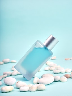 Niebieska przezroczysta butelka perfum, matowe szkło, na niebieskim tle i kamyczki obok.