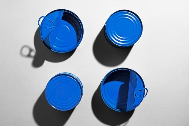 Niebieska puszka na szarej powierzchni z cieniem