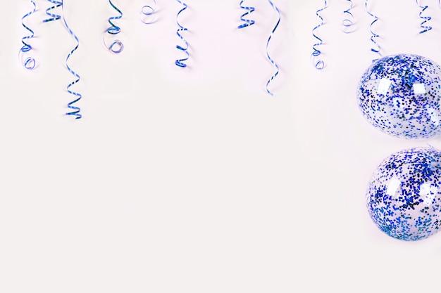 Niebieska serpentyna i balony z konfetti na jasnym tle.