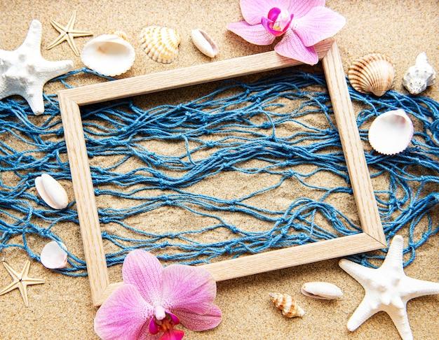 Niebieska sieć rybacka i drewniana rama na piasku plaży, podróż, koncepcja wakacji