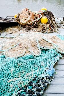 Niebieska sieć rybacka na pontonie z linami i pływakami pokrytymi porannym mrozem